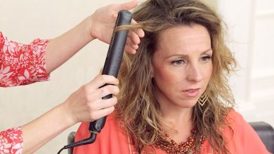 Stylist and client using a flat iron to get curls