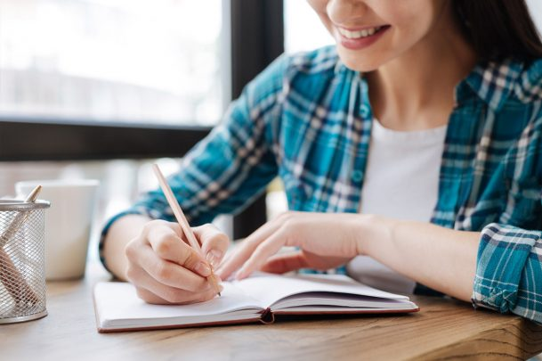 woman sitting at desk writing in a notebook