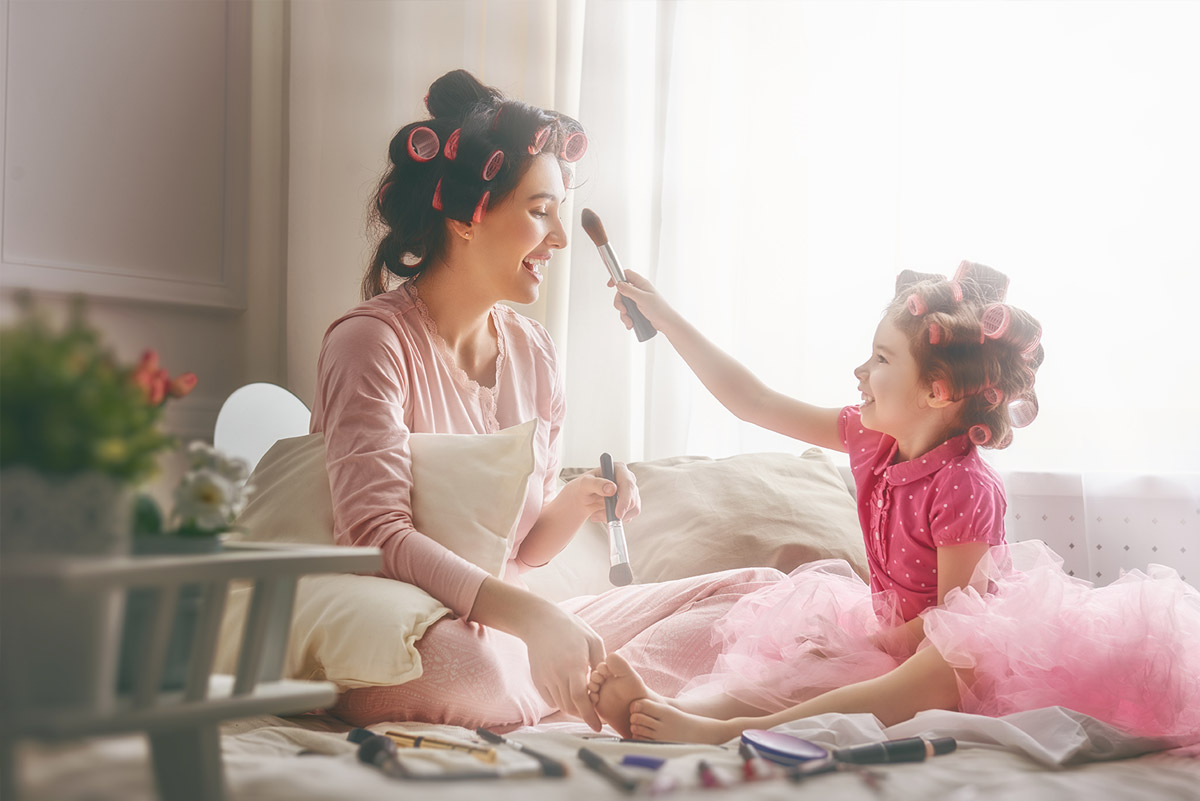 Mom sitting on floor with curlers in her hair while young daughter brushes makeup on her face
