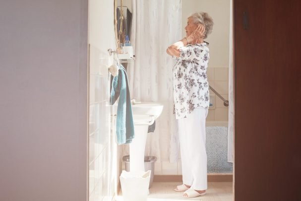 mature women over 50 standing in front of the mirror getting ready