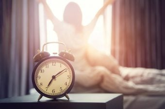 woman stretching by a sunlit window after her alarm goes off