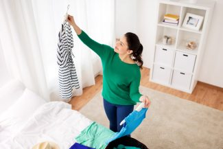 Woman in her bedroom holding up clothes she already has to create a new look