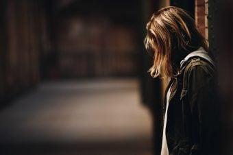 Woman looking down in a dark hallway