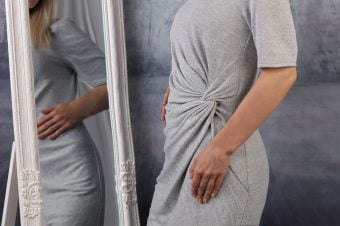 Woman in gray dress looking in the mirror - how to love your body shape