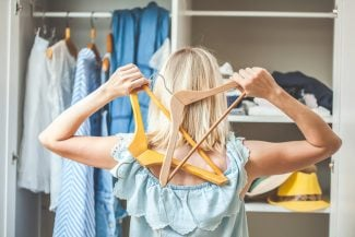 Woman looking into her closet holding hangers