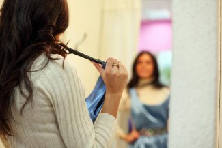 Women looking in mirror holding a blue dress