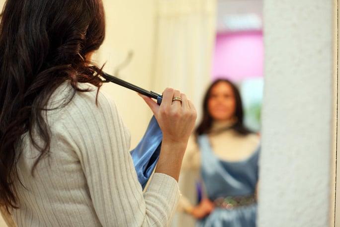 Women looking in mirror holding a blue dress