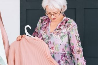 Woman with white hair and glasses looking down at a pink shirt on a hanger