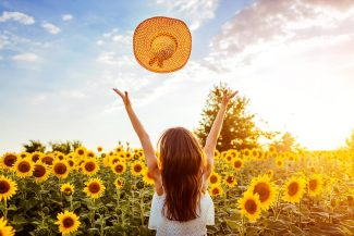 Woman throwing hat up in the air in a field of sunflowers