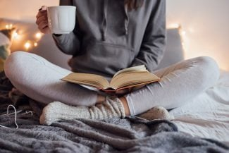 Cozy woman sitting in bed, mug in hand, reading a book.