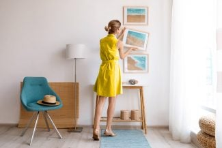 Woman in yellow dress straightening photos on a wall