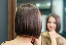 Woman with bob haircut looking at reflection in mirror