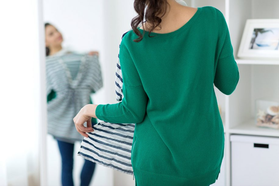 Woman in green sweater looking in mirror