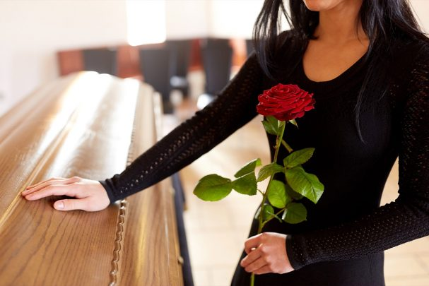 Woman at funeral wearing black dress standing by coffin holding a red rose