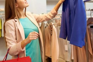 Woman choosing blue jacket at store