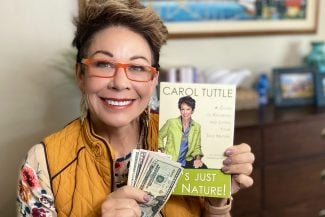 Carol Tuttle holding money with the book It's Just My Nature