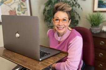 Carol in front of her laptop - how to look great on zoom