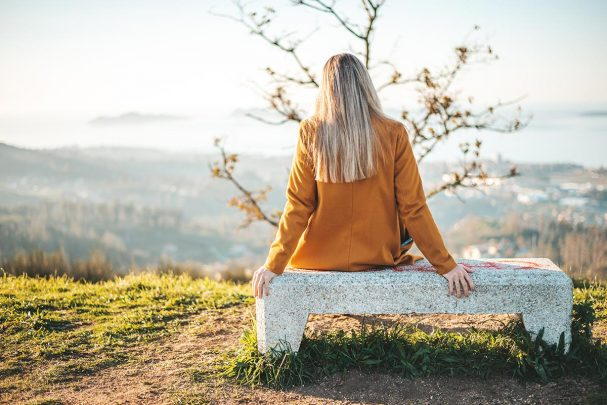 Woman in yellow coat sitting on a bench outside looking out at a nature view