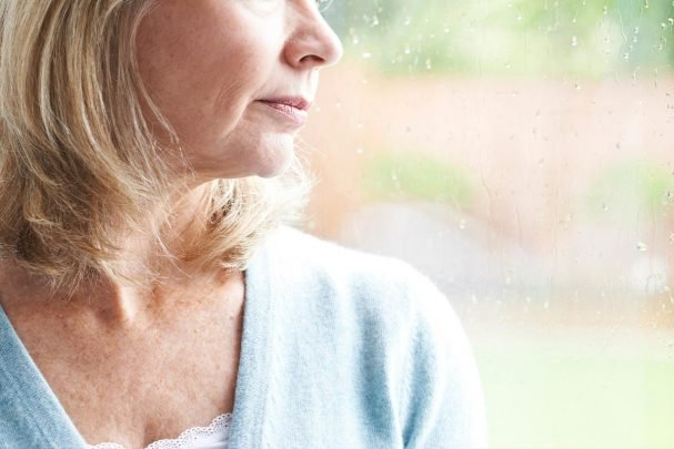 Woman in blue shirt looking out the window as it rains