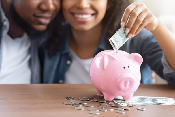 What's Your Money Type? Black couple smiling putting money in a pink piggy bank